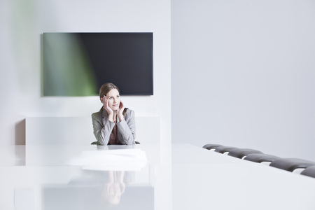 Germany,North Rhine Westphalia,Cologne,Businesswoman Sitting In Conference Room,Looking Away LANG_EVOIMAGES