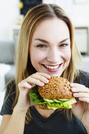 Germany,Bavaria,Munich,Portrait Of Young Woman Holding Burger,Close Up