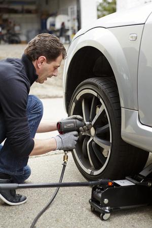 Germany,Bavaria,Kaufbeuren,Mature Man Changing Car Tire