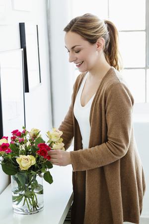 Alemania, baviera, munich, mujer joven, arreglar las flores, en, florero, sonriente