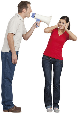 Mid adult man with megaphone shouting on young woman