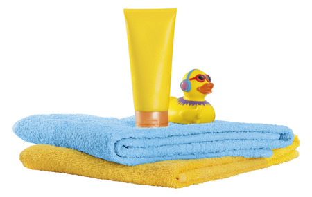 Sunscreen with beach towel and rubber duck on white background,close up LANG_EVOIMAGES
