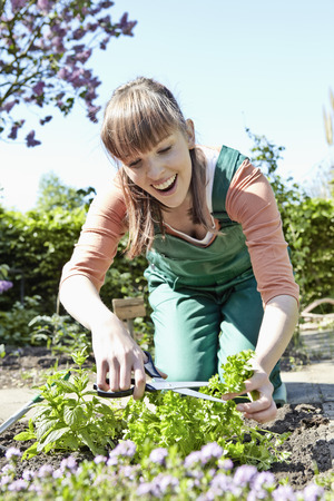 Germany,Cologne,Young woman cutting leaves with shears,smiling