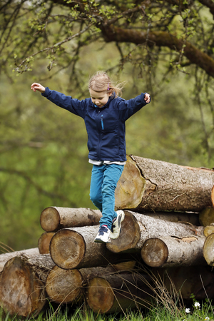 Germany,Baden Wuerttemberg,Girl jumping from wooden logs