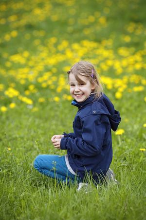 Germany,Baden Wuerttemberg,Portrait of girl sitting in meadow,smiling