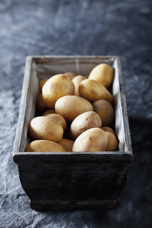 Potatoes in wooden basket on textile,close up