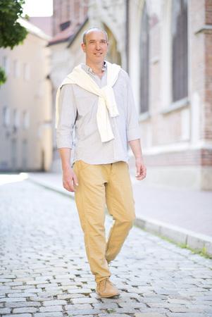 Germany,Bavaria,Mature man walking,smiling LANG_EVOIMAGES