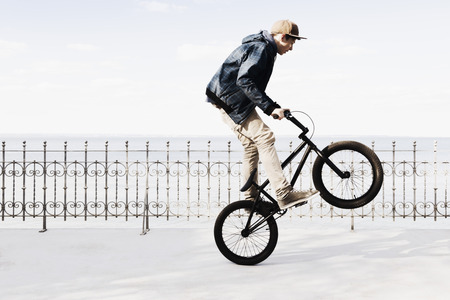 Germany,Schleswig Holstein,Teenage boy jumping with BMX bike LANG_EVOIMAGES