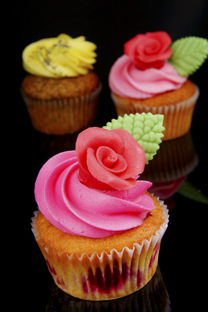 Cup cake with buttercream topping on black background,close up LANG_EVOIMAGES