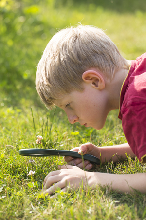 Germany,Bavaria,Boy looking through magnifying glass in garden LANG_EVOIMAGES
