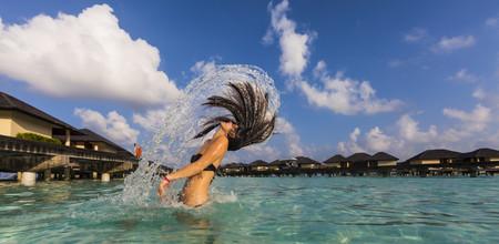 Maldives,Young woman splashing wet hair in lagoon