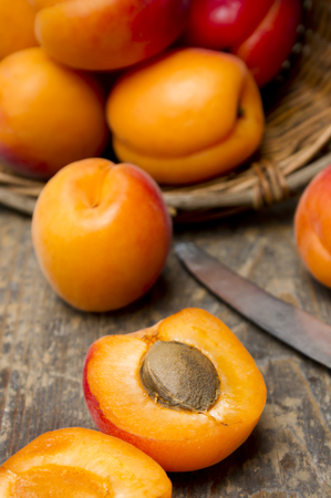 Basket of apricots with knife on wooden table,close up