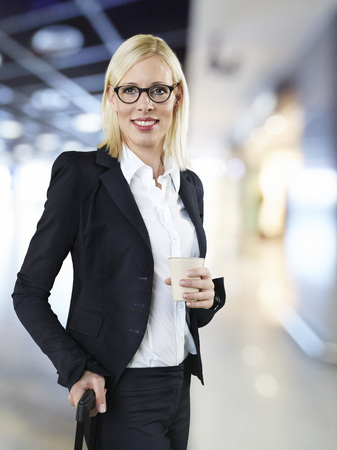 Businesswoman holding disposable cup and briefcase at airport,smiling
