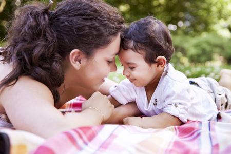 Mother cuddling her baby boy on blanket,smiling