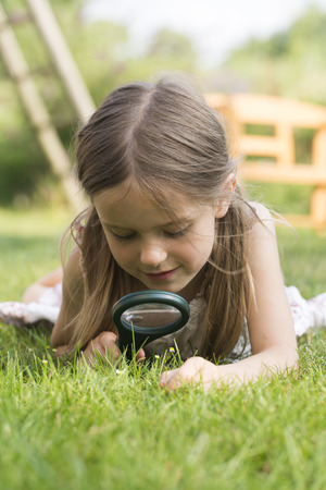 Germany,Bavaria,Girl looking through magnifying glass in graden