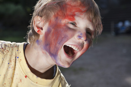 Germany,North Rhine Westphalia,Cologne,Boy playing with colours in playground,smiling
