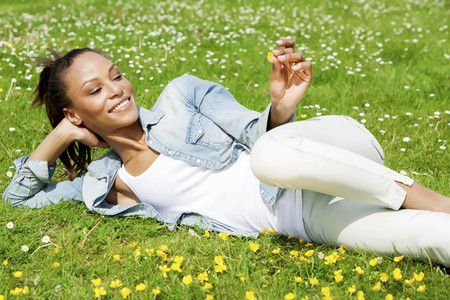 Germany,Young woman lying on flower meadow. smiling