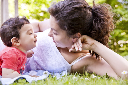 Mother cuddling her baby boy on grass