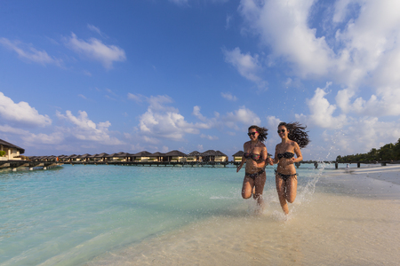 Maldives,Young woman and teenage girl running on beach