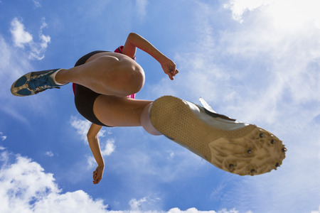 Germany,Young woman doing long jump in track