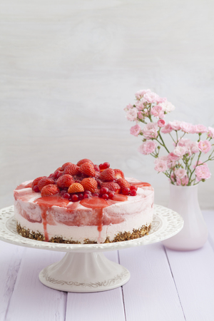Strawberry cheesecake with fresh strawberries and redcurrants on wooden table,close up