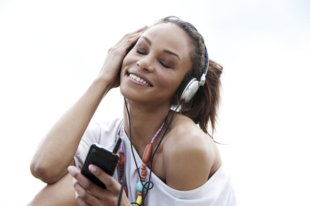 Germany,Young woman listening music with head phones,smiling LANG_EVOIMAGES