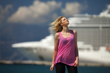 Greece,Young woman posing in front of cruise ship