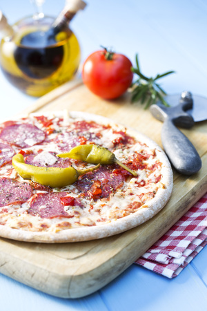 Pizza with salami on chopping board,close up LANG_EVOIMAGES
