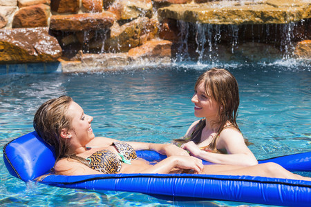 Young women relaxing on float in swimming pool,smiling LANG_EVOIMAGES