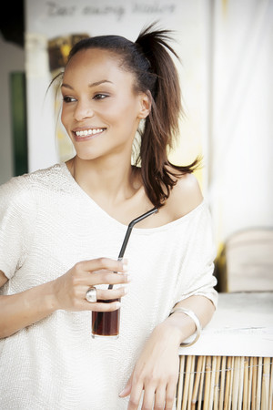 Germany,Young woman holding glass of coke,smiling