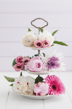 Summer flowers arranged on cake stand LANG_EVOIMAGES