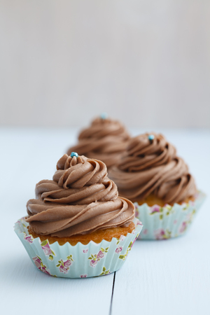 Cupcakes topped with chocolate buttercream on wooden table,close up