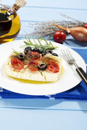 Feta,tomatoes,olives and rosemary in plate with fork LANG_EVOIMAGES