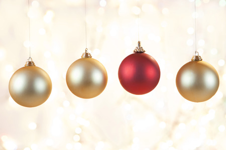 Christmas baubles hanging in front shiny background,close up