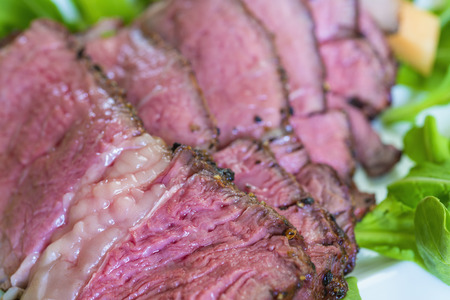 Sliced rib eye steak garnished with arugula and cantaloupe on plate,close up