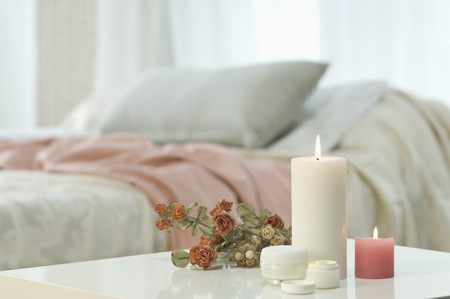 Candles,skin cream and bunch of roses on table with bed in background LANG_EVOIMAGES