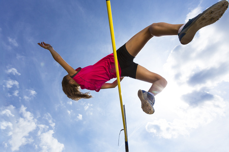 Germany,Young woman athlete jumping hurdles on track