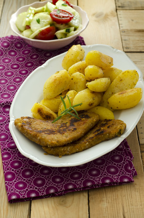 Fried potatoes with vegetarian Schnitzel and salad in background
