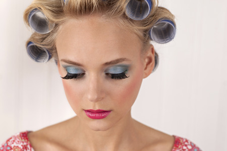 Young woman with curlers,looking down,close up LANG_EVOIMAGES