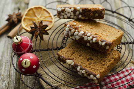 Gingerbread cake with christmas baubles and dried orange,spice on wooden table,close up