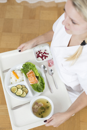 Germany,Young woman holding patient tray with main meal,close up