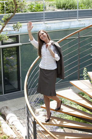 Businesswoman on spiral staircase waving her hand