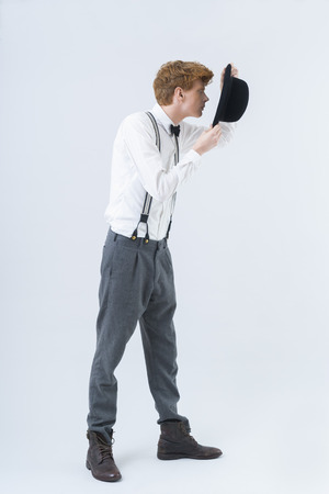 Young man showing magic with hat LANG_EVOIMAGES