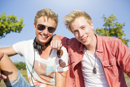 Germany,two friends listening to music with headphones
