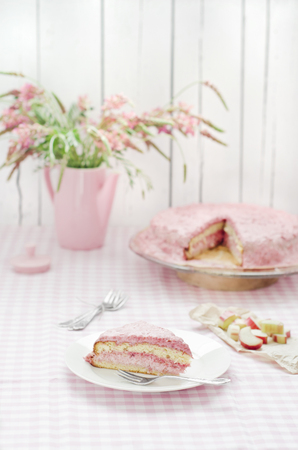 Rhubarb and raspberry cream cake with pink flowers on table,close up