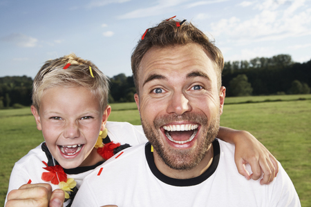 Germany,Cologne,Father and son supporting their soccer team LANG_EVOIMAGES