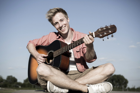 Germany,Young man playing guitar in park LANG_EVOIMAGES