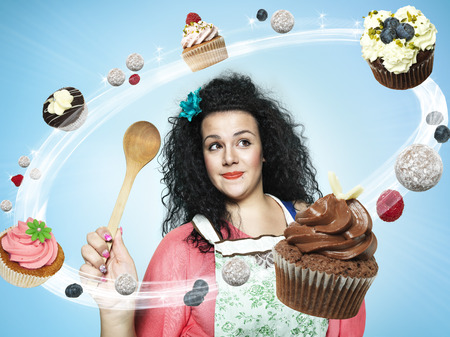 Smiling young woman looking at flying cup cakes,Composite