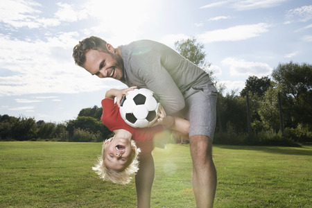 Germany,Cologne,Father and son playing soccer LANG_EVOIMAGES