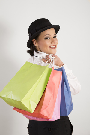 Portrait of young woman holding shopping bags,smiling LANG_EVOIMAGES